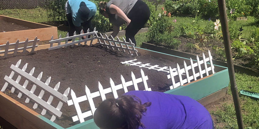 Painting raised beds in the Community Garden